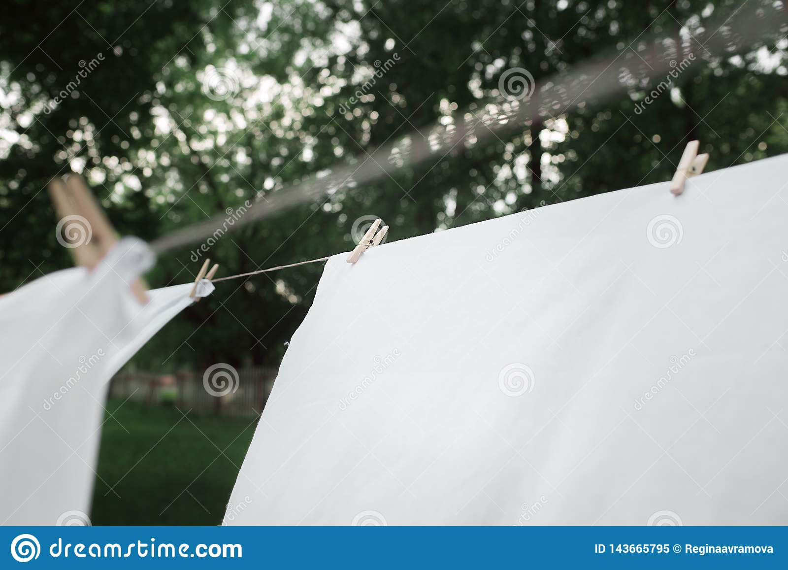 Washed towels are hanging on the rope. Linen is dried. Clothespin on a towel that is dried. Drying linen in the garden