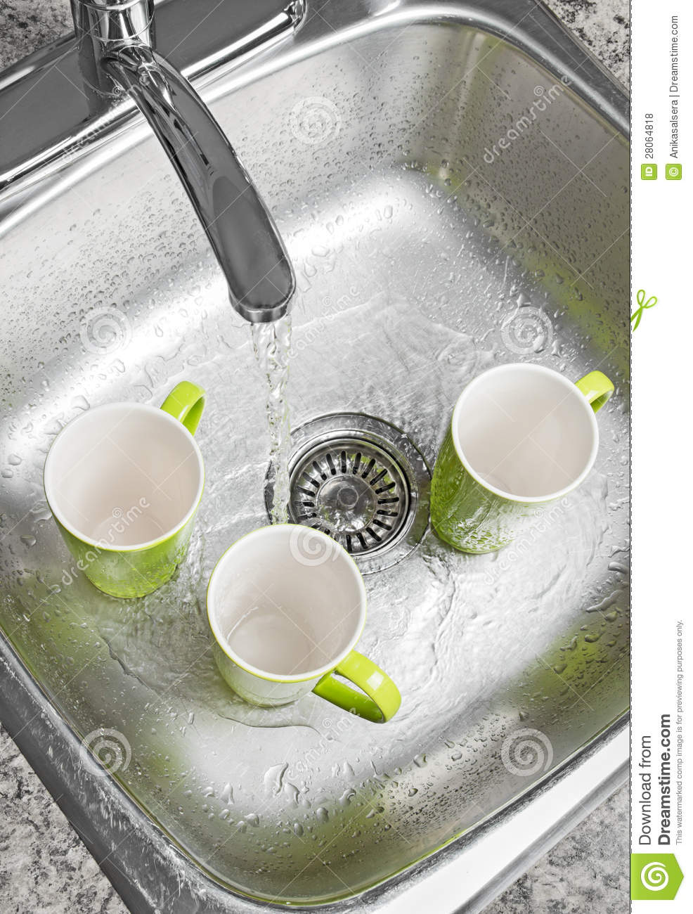 Washing green cups in the kitchen sink. Water running from the tap.