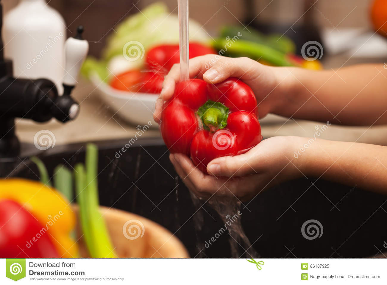 Washing fresh vegetables for a healthy salad - the red bell pepper, shallow depth