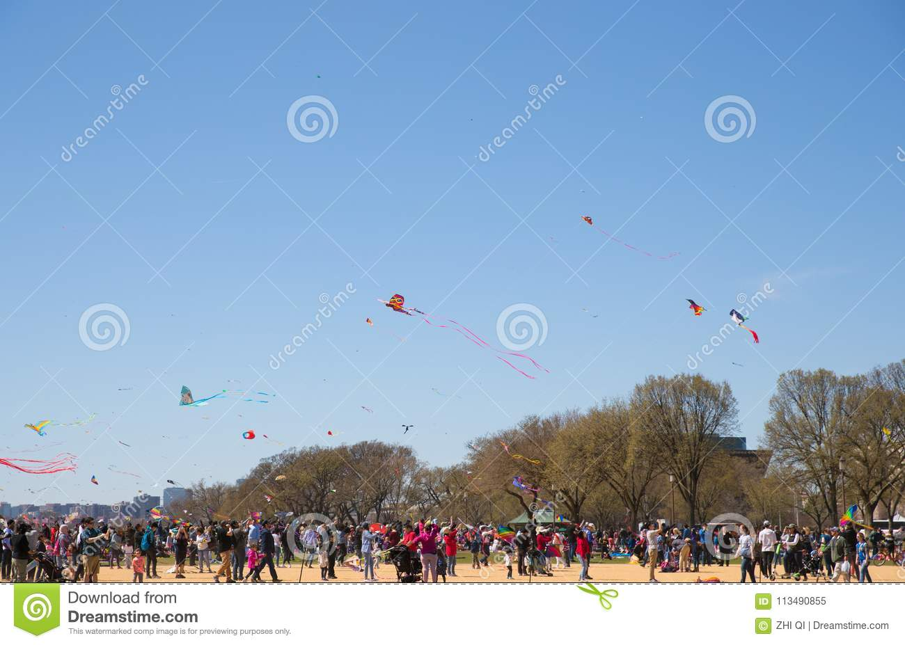 A Large Crowd Of Adults And Children Flying Kites At The