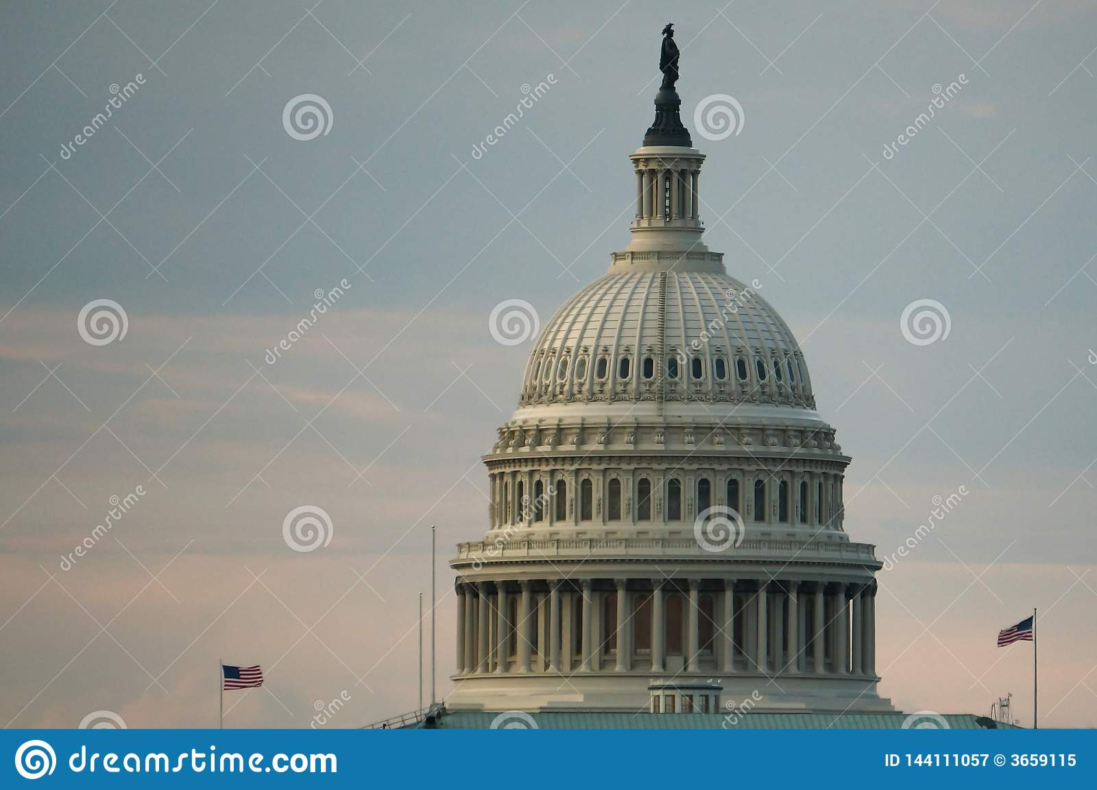Washington, DC, USA. 08 18 2018. US Capitol dome with two flying flags at dawn or twilight.