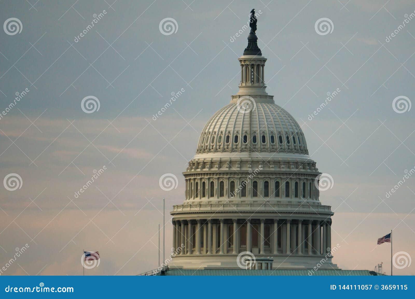 Washington, gelijkstroom, de V.S. 08 18 2018 Het Capitoolkoepel van de V.S. met twee vliegende vlaggen bij dageraad of schemering