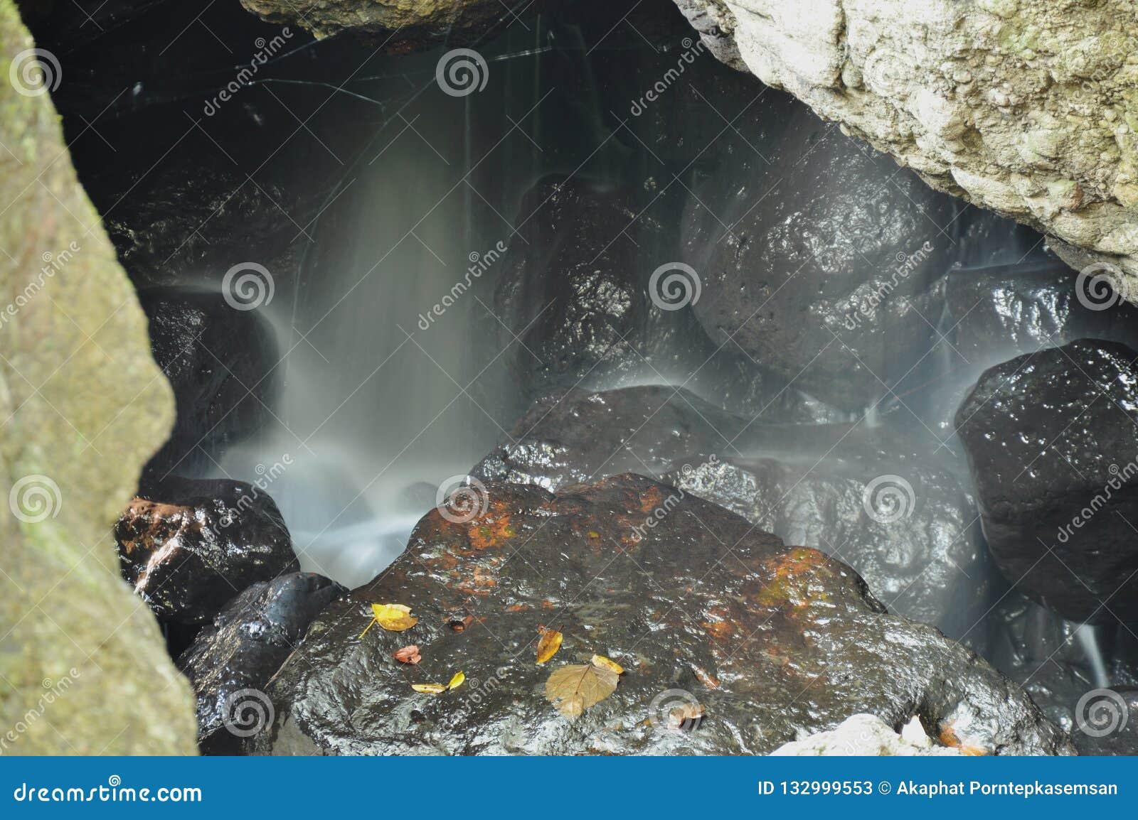 Wasserfall in der Höhle hinter Felsen im Wald