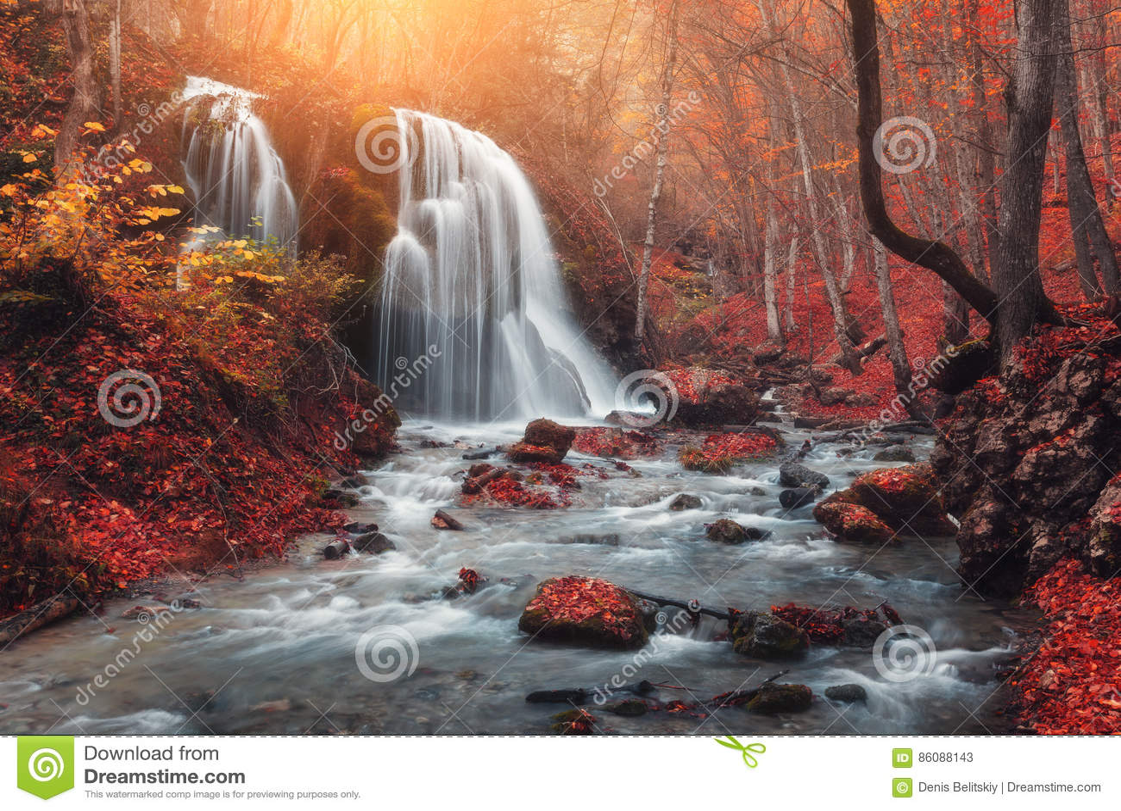 Wasserfall in Gebirgsfluss im Herbstwald bei Sonnenuntergang