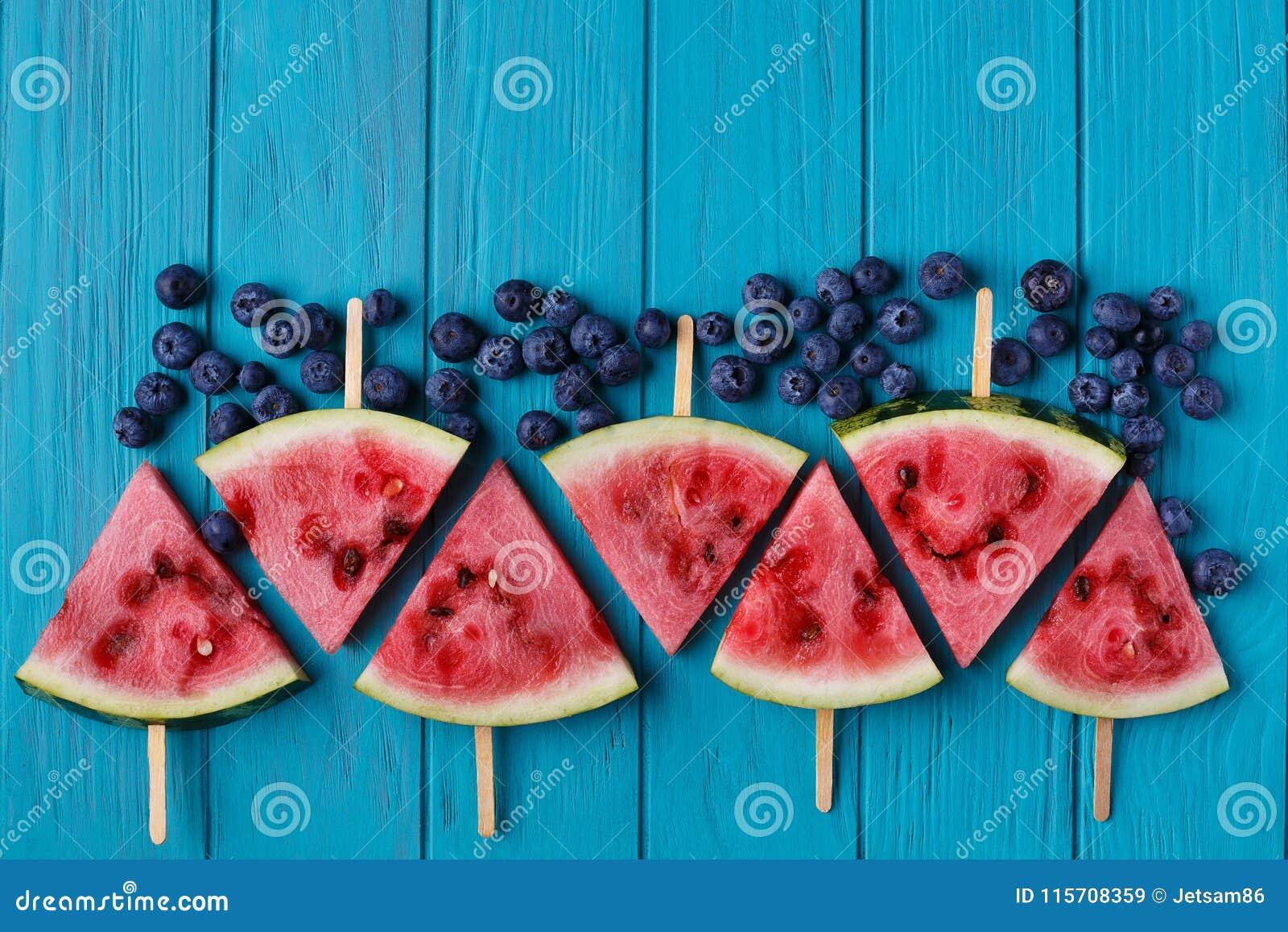 Wassermelonenscheibenpopslices und -blaubeeren auf einer blauen hölzernen Rückseite
