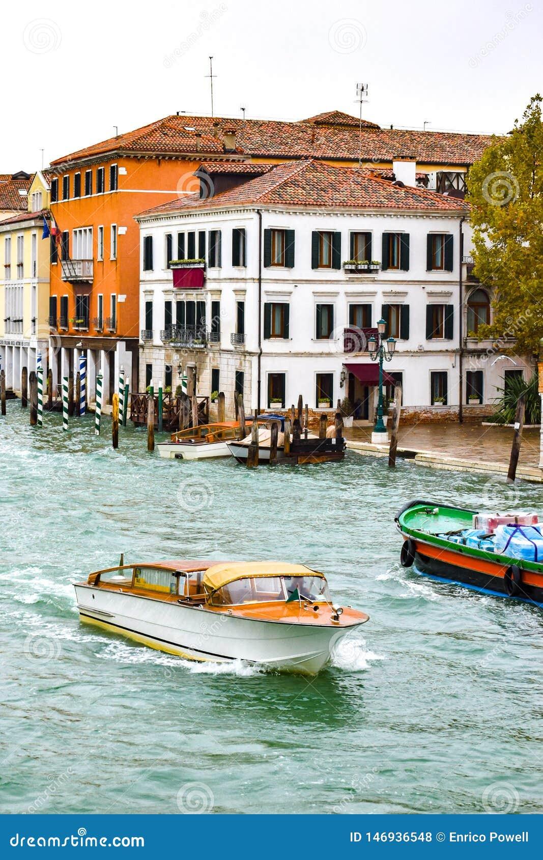 Wassertaxi und ein Boot, welches die Waren, segelnd durch Grand Canal in Venedig, Italien transportiert