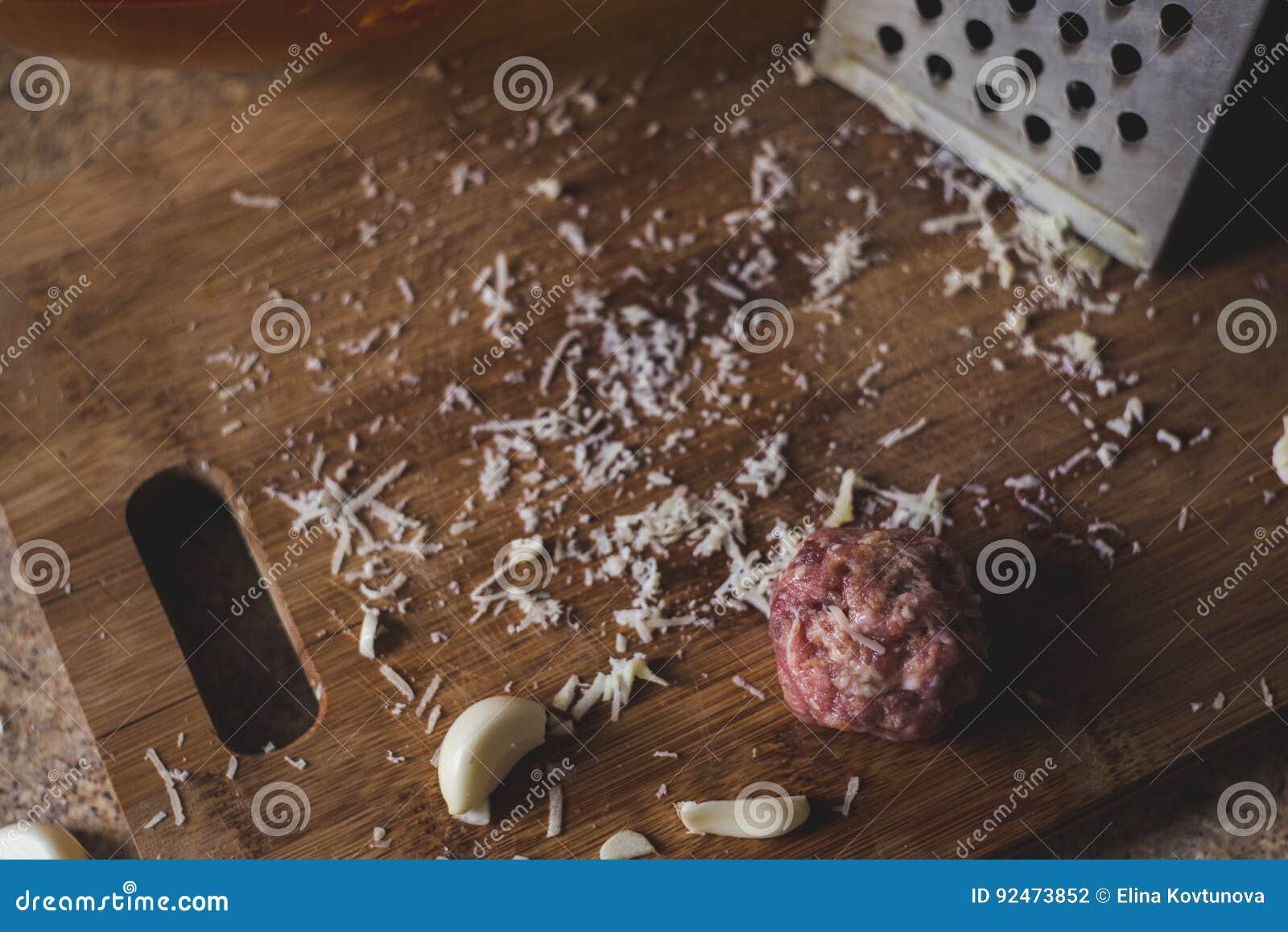 Wat kaas, vlees en knoflook op een houten broodplank