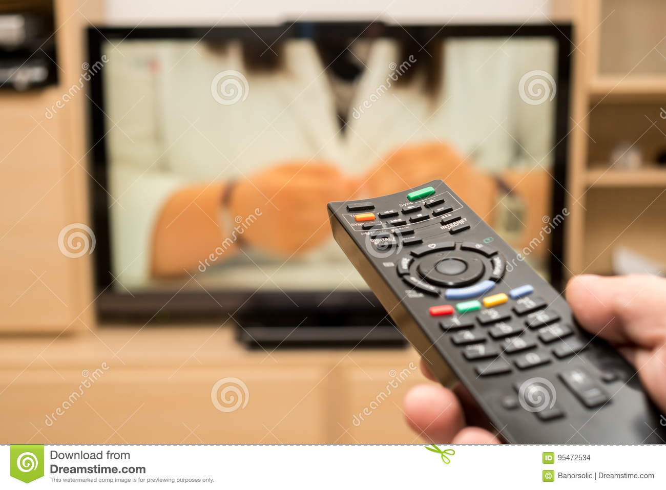 Watching TV And Using Black Modern Remote Controller  Hand