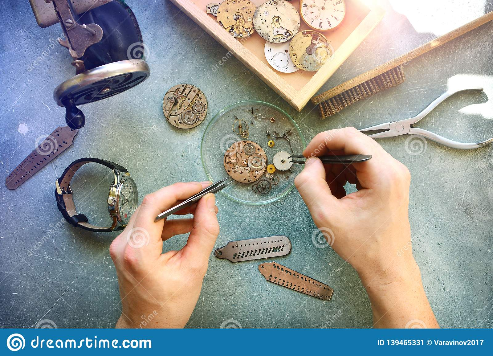 Watchmaker at work in workshop. Flat lay. Workplace of watch repairer. Process of repair mechanical watches.