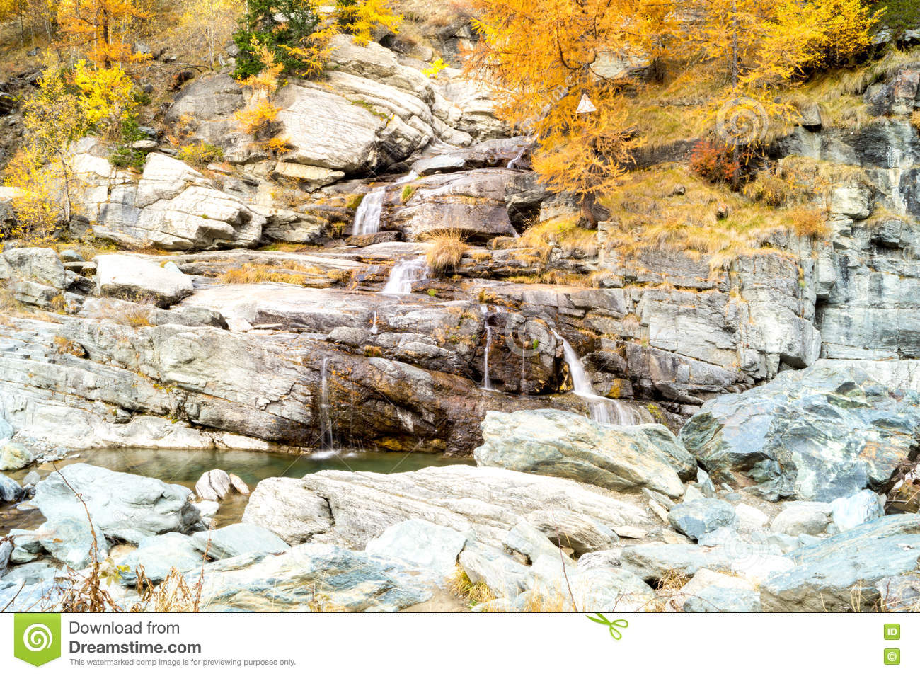 Water cascading over rocks, waterfall and autumn colors in the mountains, yellow and red trees