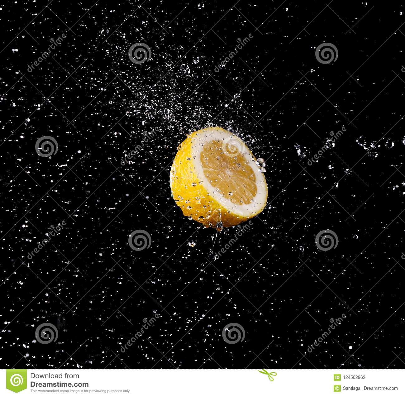 Water drops splashing onto a lemon