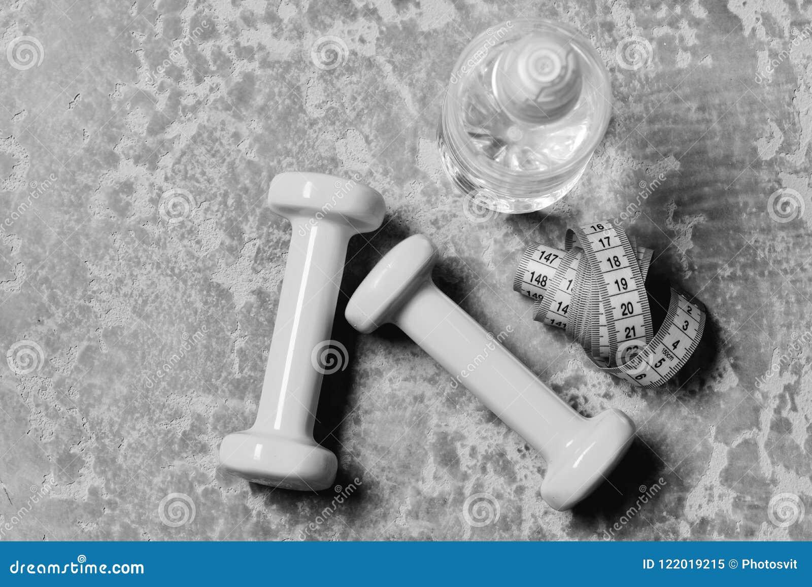 Water en maatregelenband dichtbij plastiek barbells Training en verfrissing
