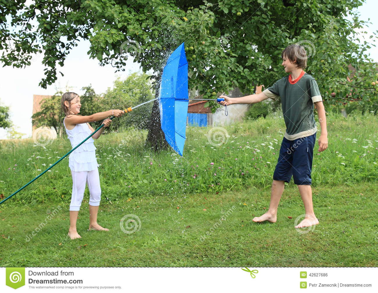 ... water with garden hose against a boy with blue umbrella as a shield
