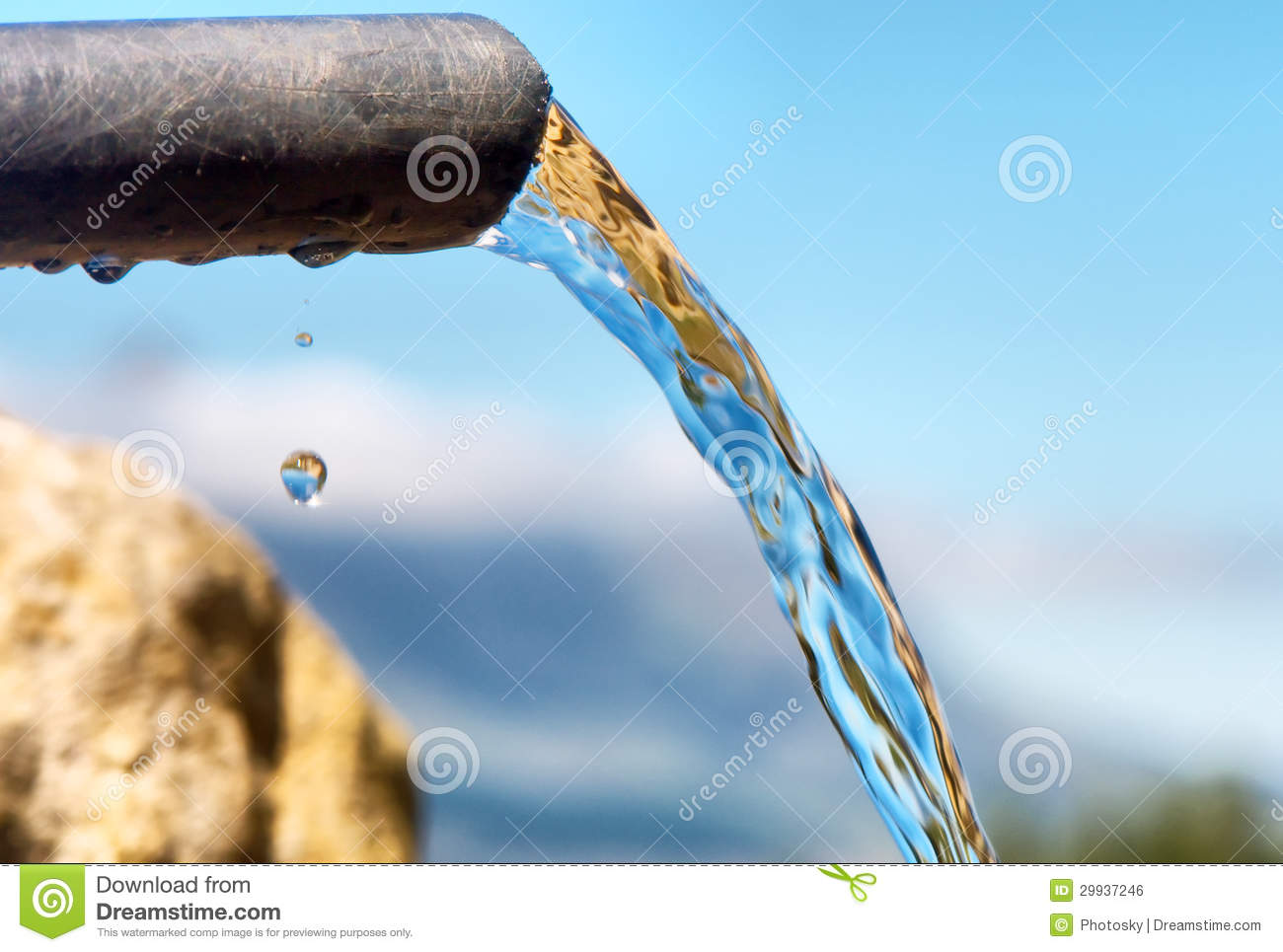 Water Flowing From Pipe Against Blurred Mountains Stock