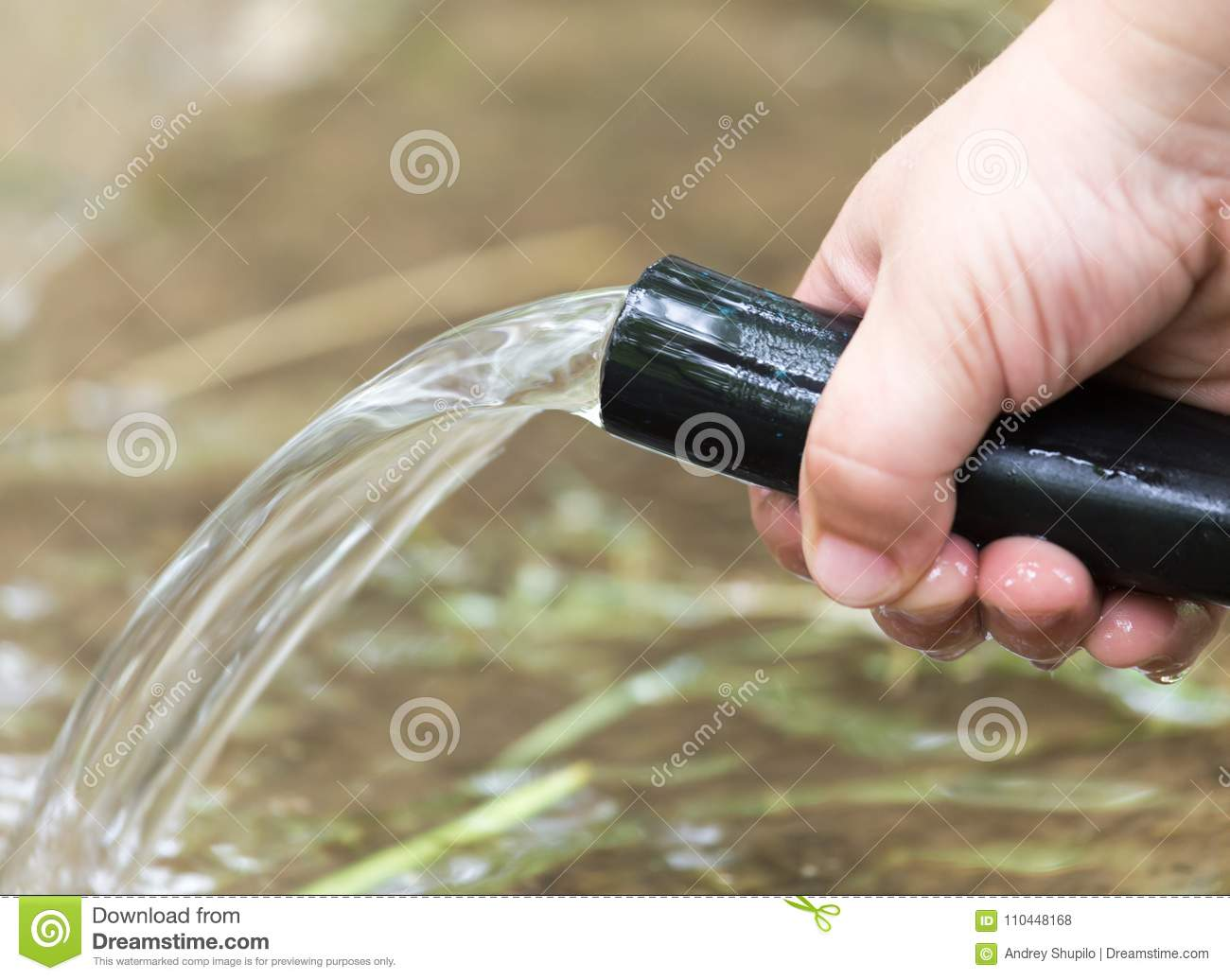 Water from a hose in hand