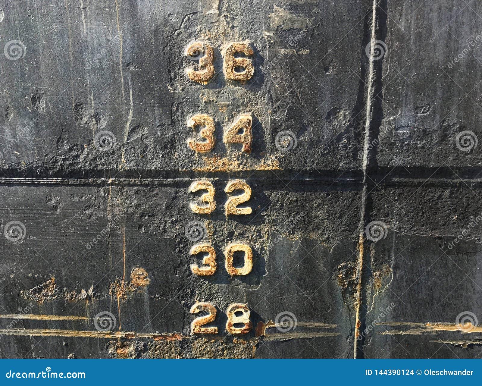 Water level depth gauge number markings on an old black ship hull fragment