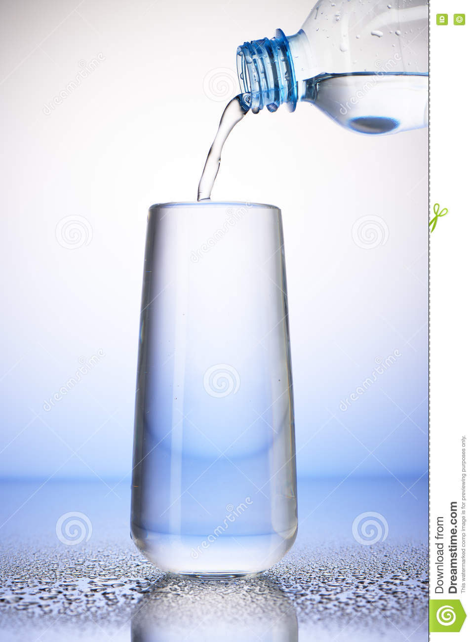 Water pouring from plastic bottle into full drinking glass