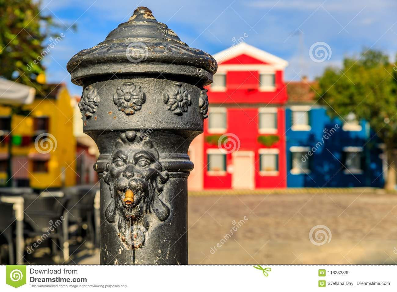 Water pump and colorful houses in Burano island near Venice Ital