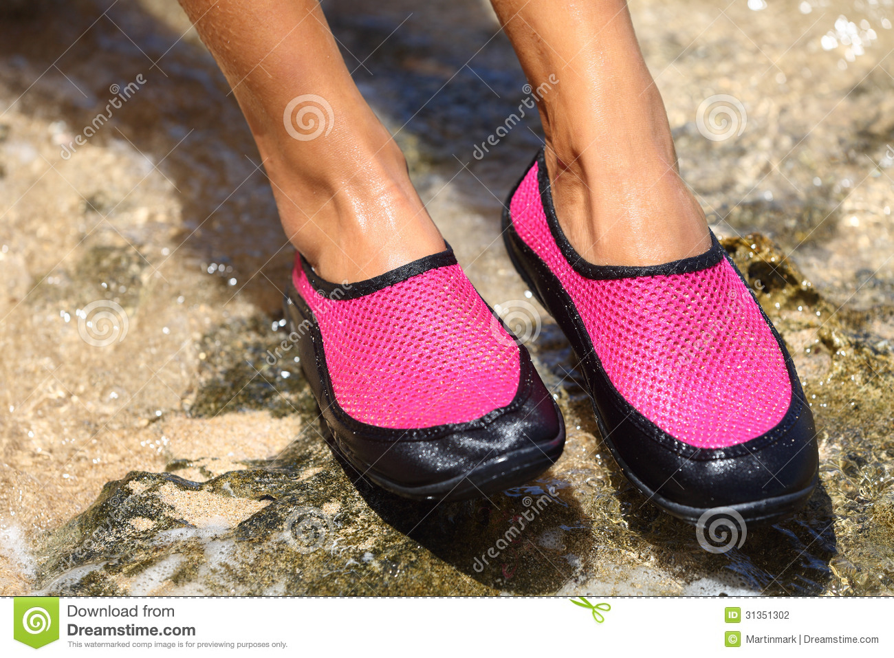 Water shoes   swim shoe in Pink neoprene on rocks in water on beach.  Closeup detail of the feet of a woman wearing bright pink neoprene water  shoes standing ... 40952efeb448