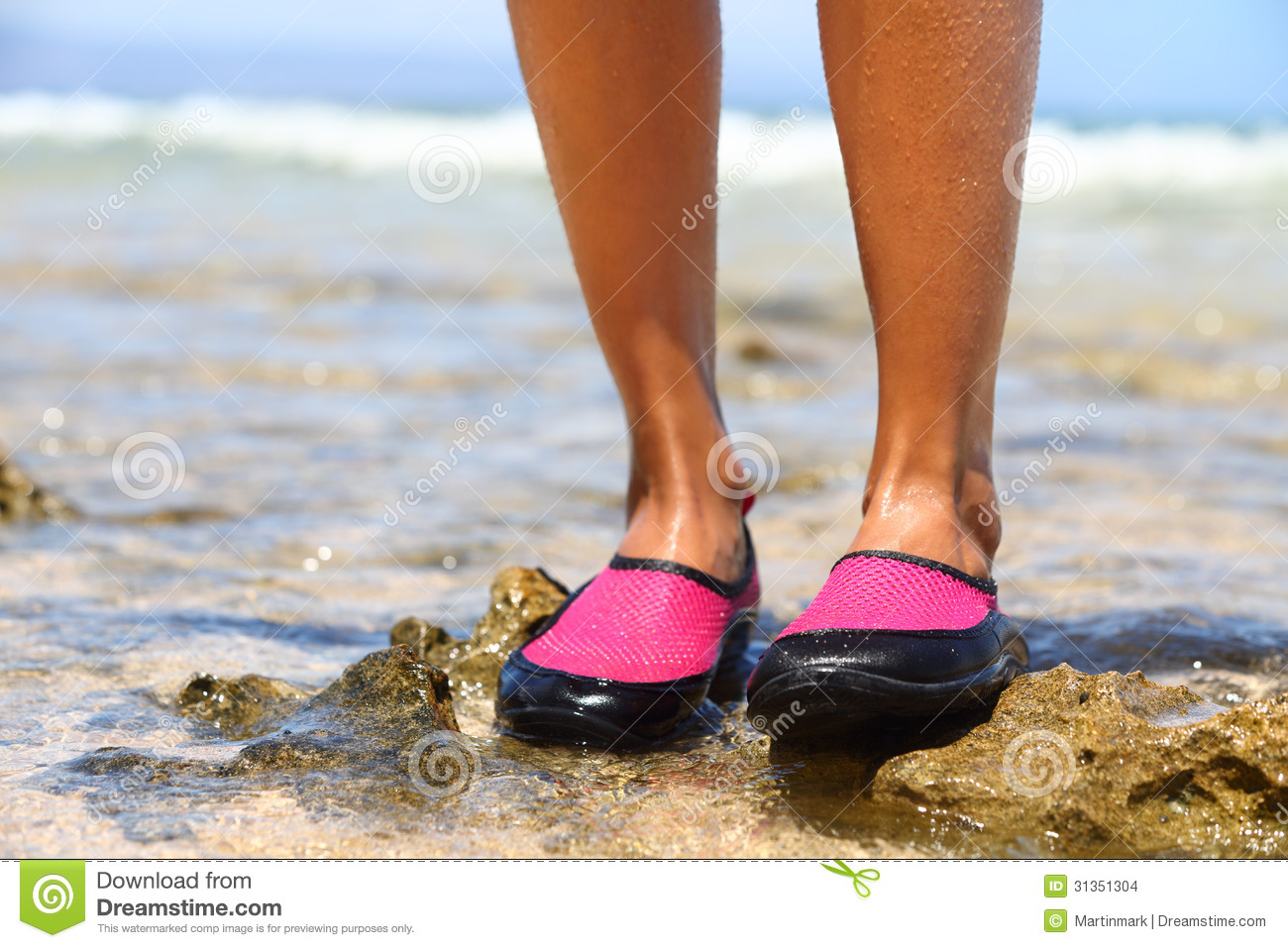 Water shoes   swimming shoe in Pink neoprene on rocks in water on beach.  Closeup detail of the feet of a woman wearing bright pink neoprene water  shoes ... e0a4602cc54a