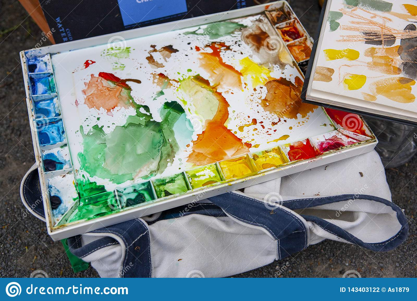 Colorful used water color pallette with blotches of paint patterns and markings