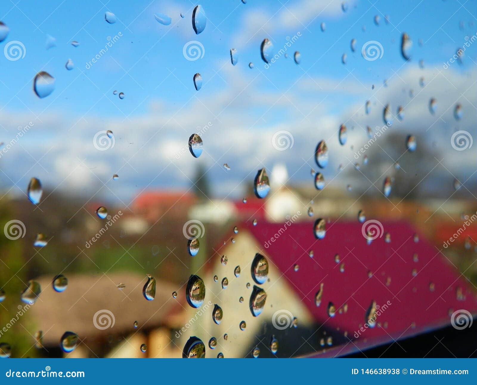 Waterdalingen na regen op vensterglas