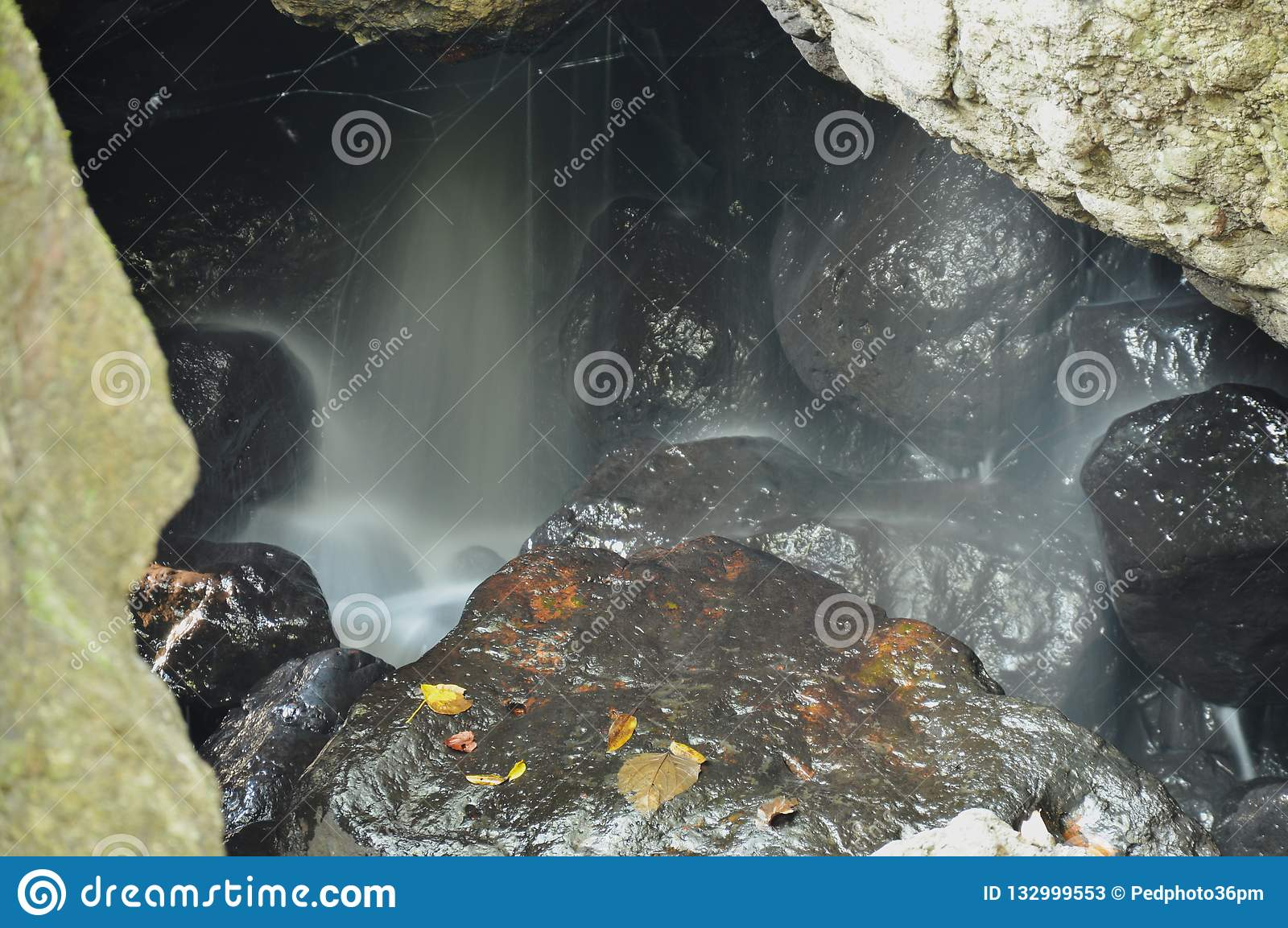 Waterfall in cave behind rock in forest