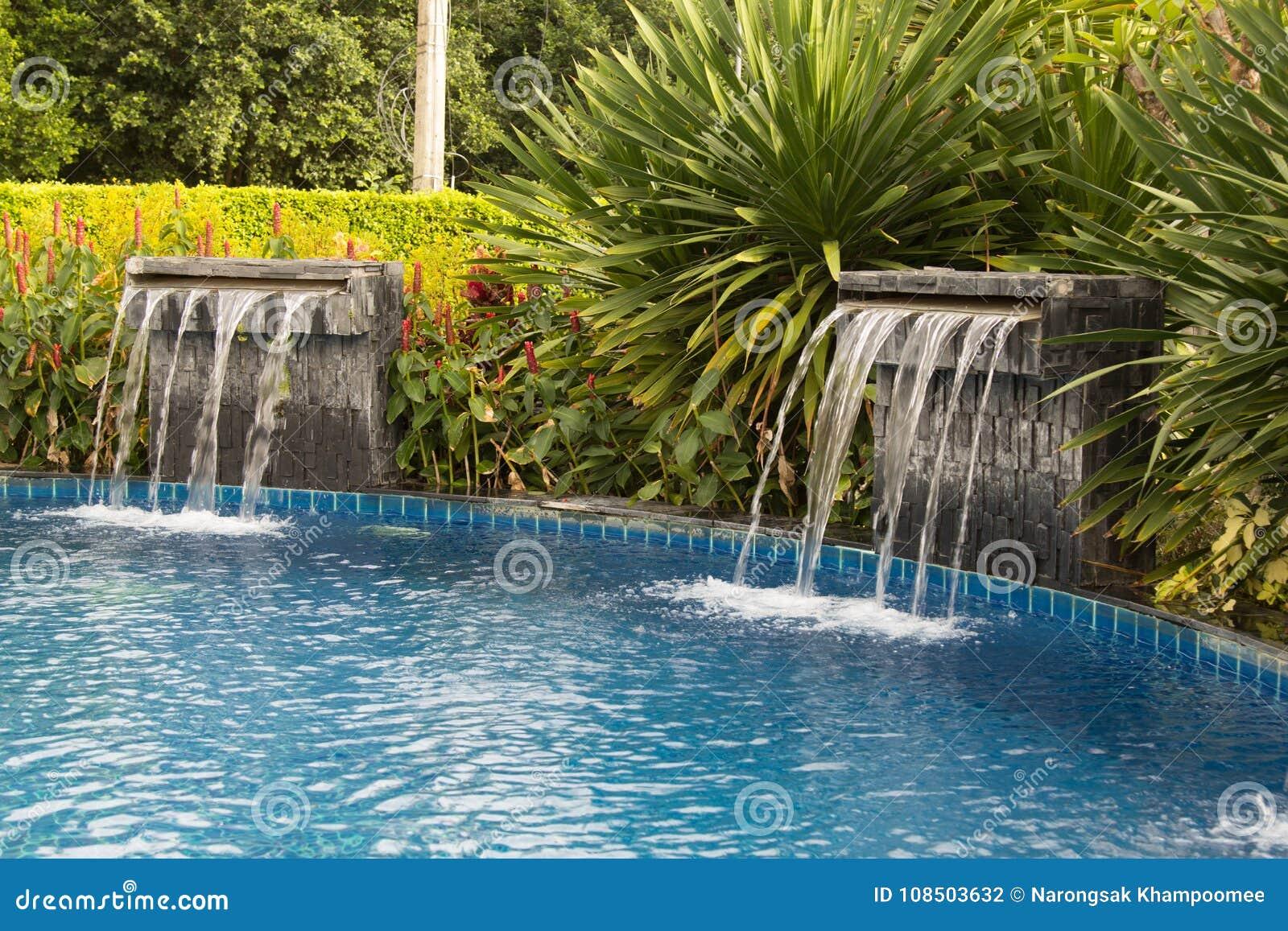 Waterfall Falling In A Blue Lagoon Swimming Pool In Hotel. Stock ...
