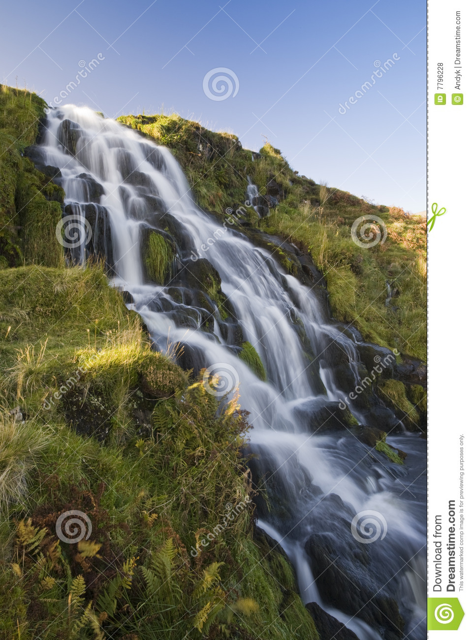 Waterfall flowing down hill with blue sky