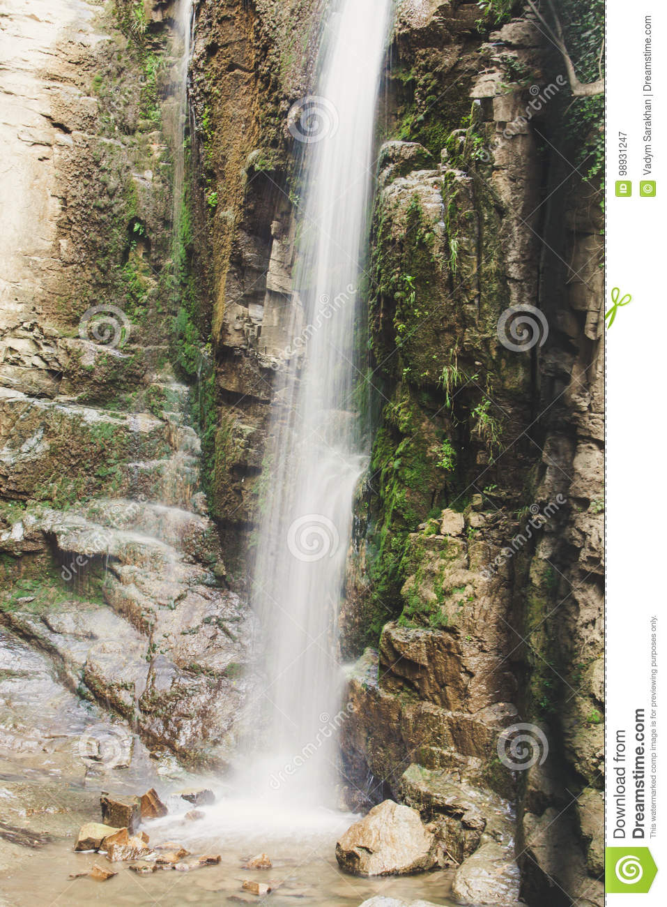 Waterfall in the mountains. Water falls from the mountain down to the rocks. It is photographed on an excerpt.