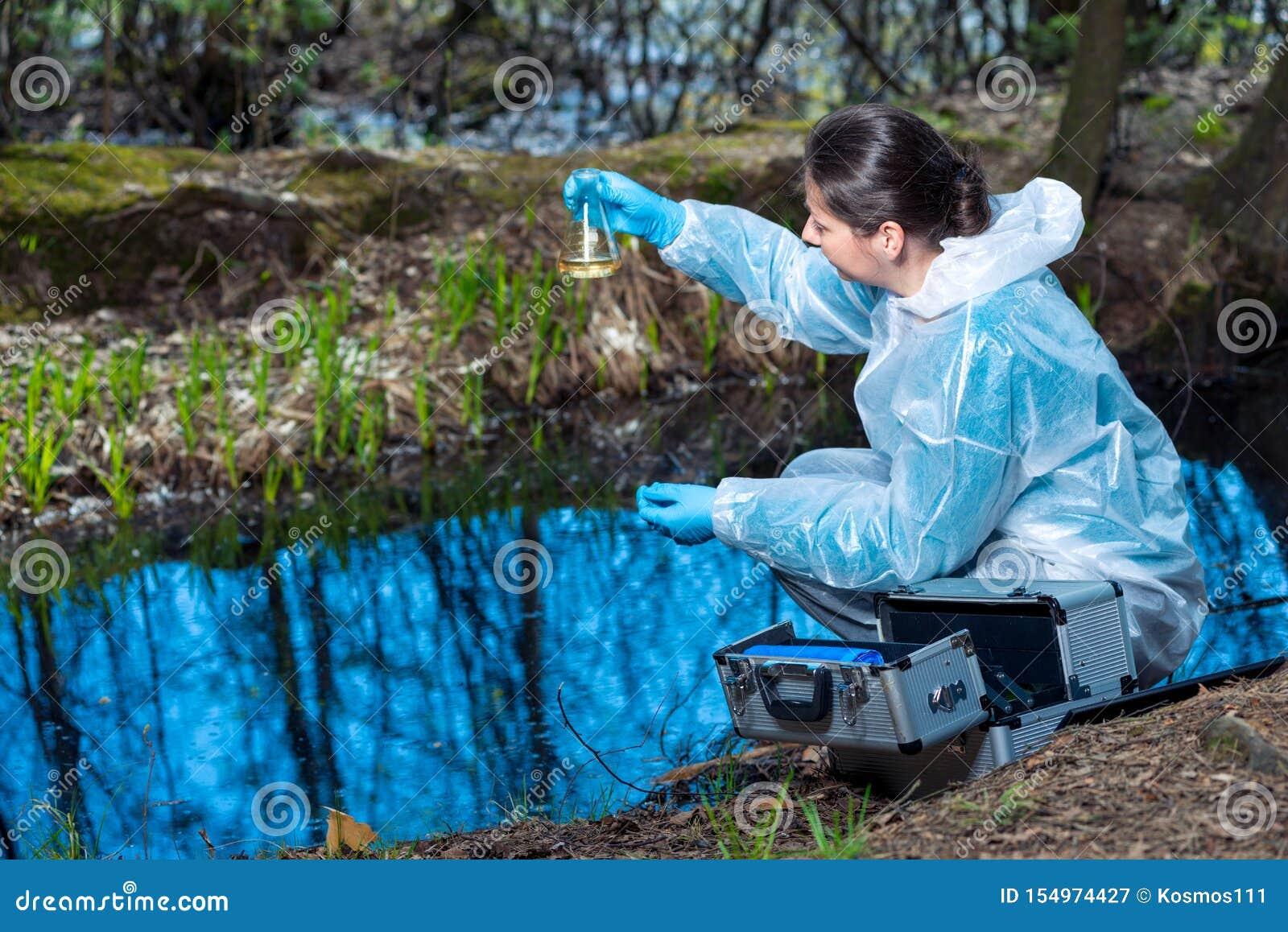 Watersteekproef van een bosrivier in een fles in de handen van een ecologist