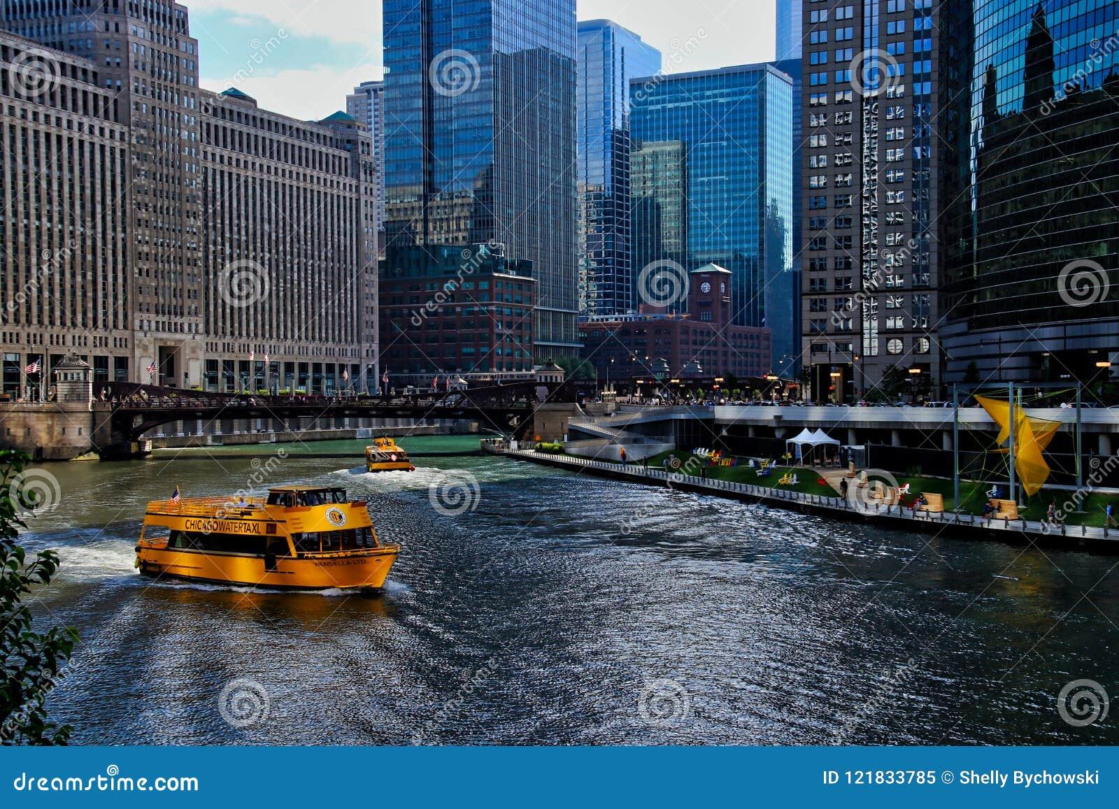 Watertaxis vervoeren de forenzen van het ochtendspitsuur over de Rivier van Chicago, met mening van kunst en zitkamerstoelen op r