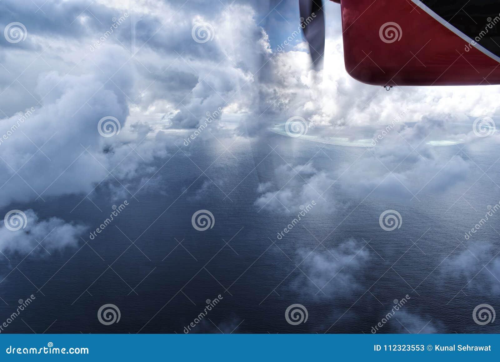 Watervliegtuig die door de wolken over Maledivische eilandoceaan vliegen