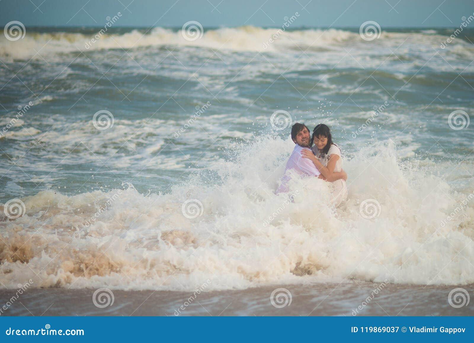 Wave ha spazzato le persone appena sposate Sposa e sposo che posano nel mare