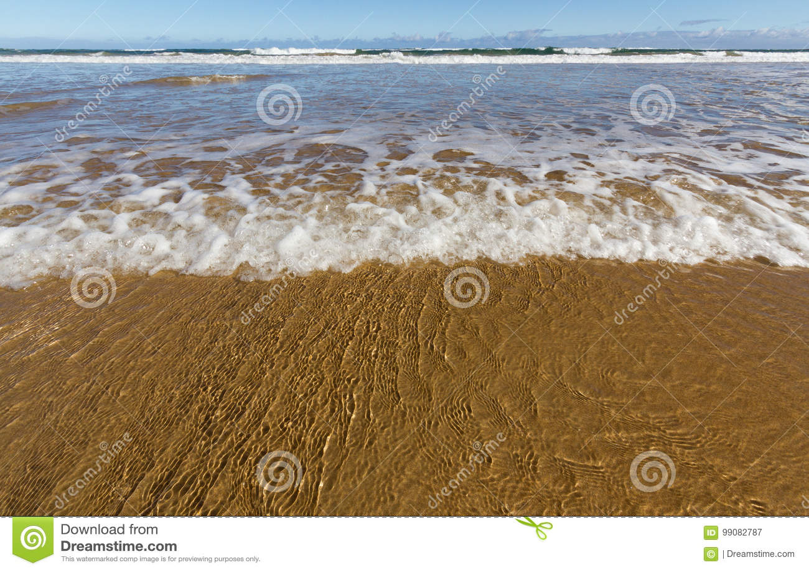 Wave laps a golden sand beach