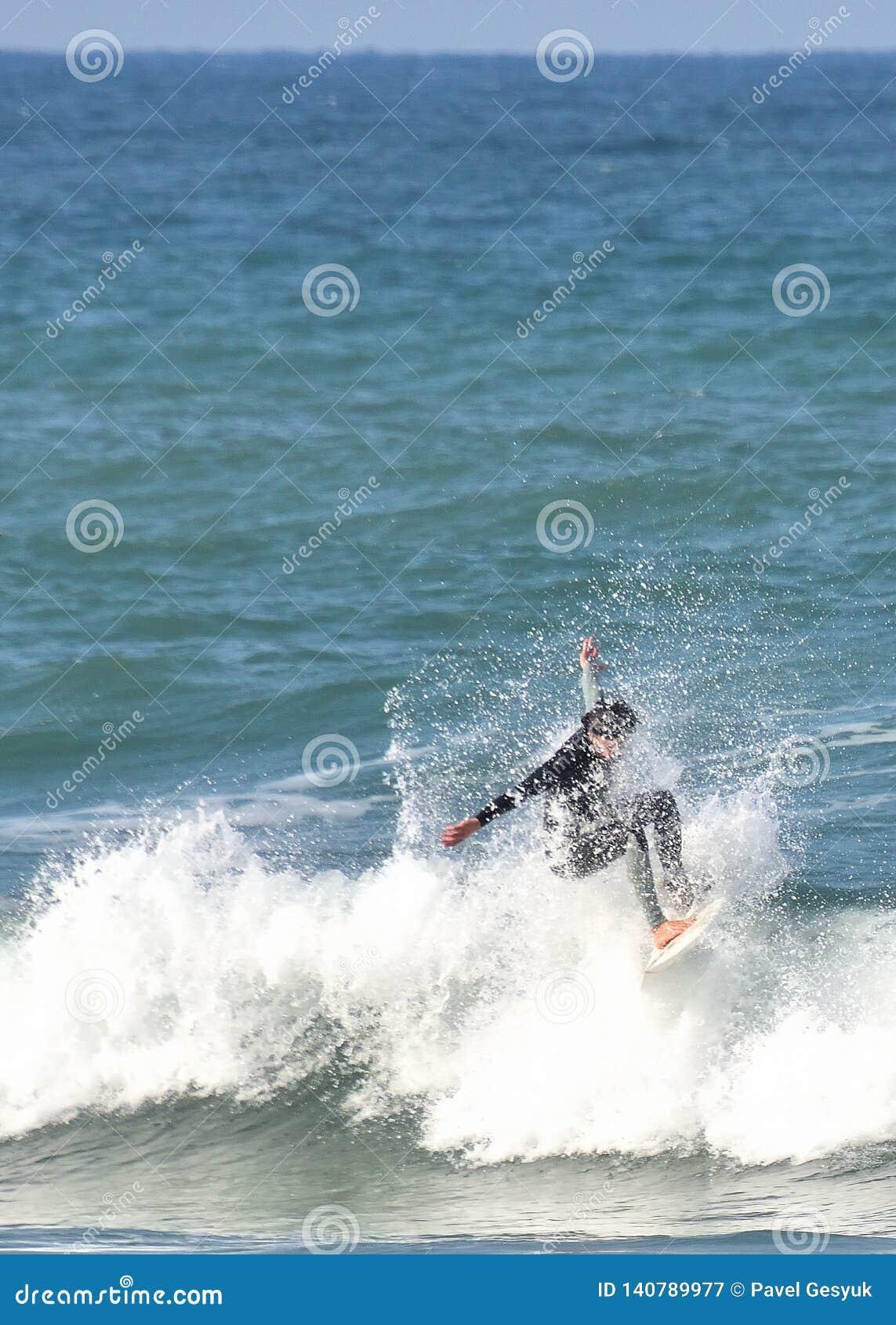 Wave surfer rides within a splash