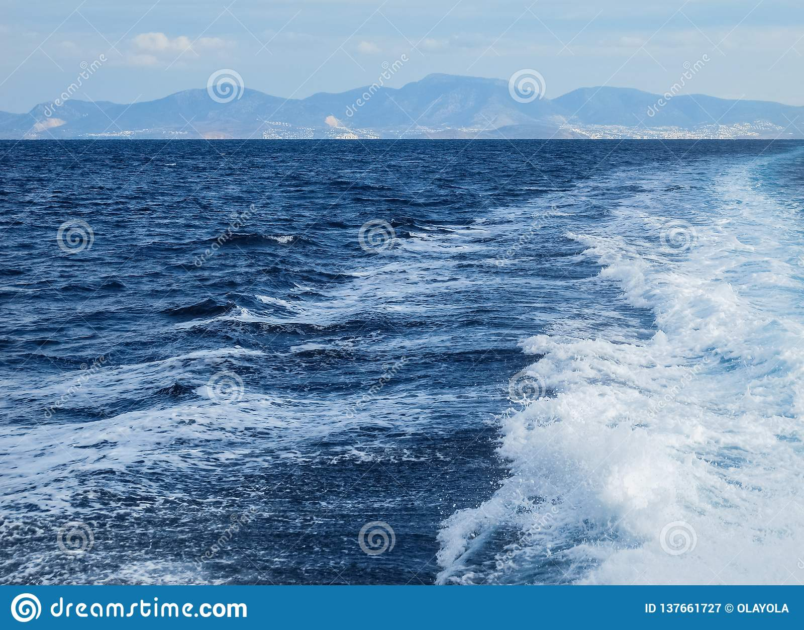 The waves and foam from a boat in a bright summer day. Islands and mountains in the background. Summer vacation