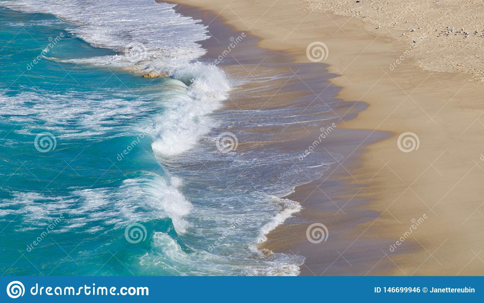 Waves lapping onto a sandy beach - image