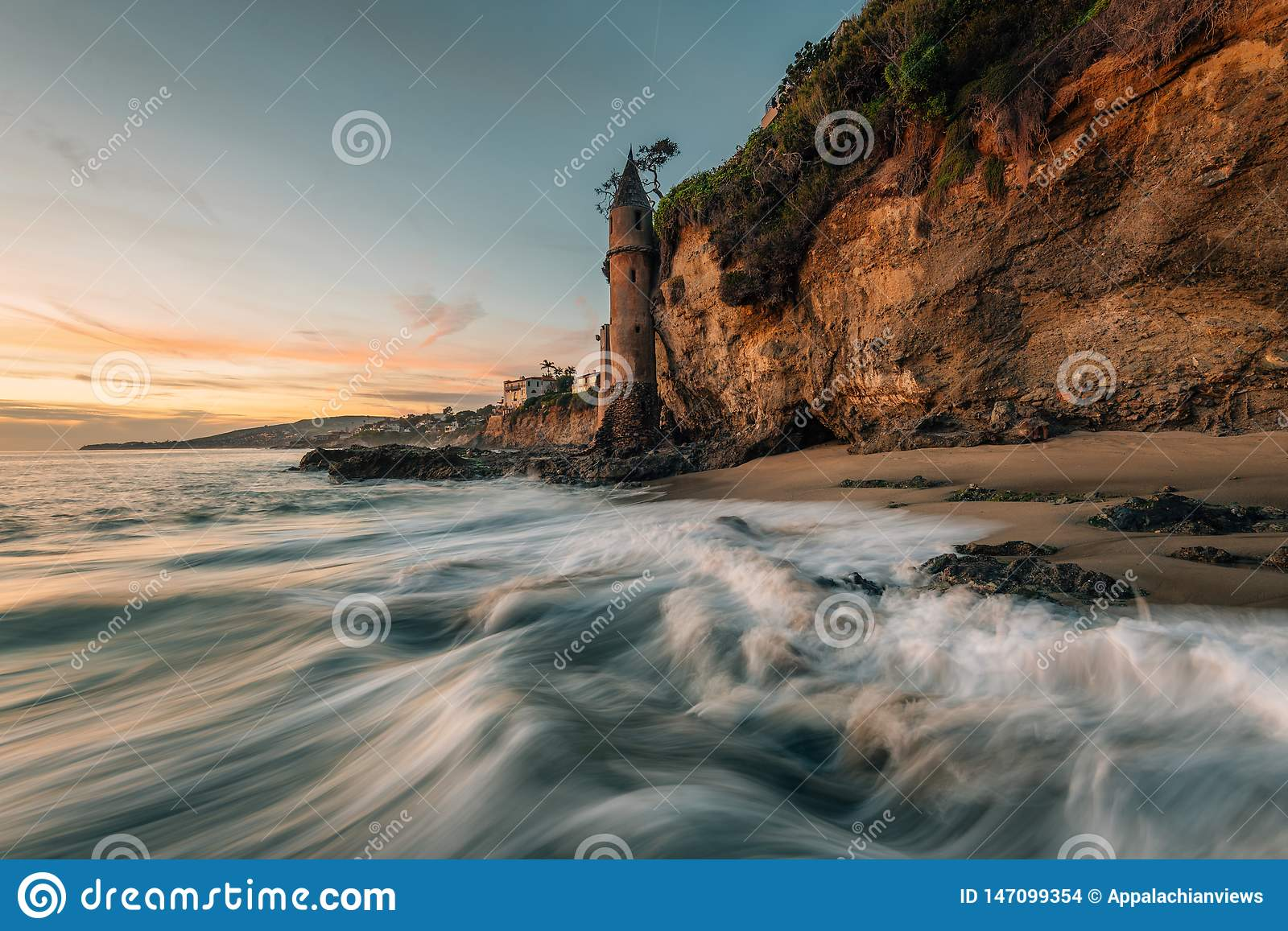 Waves in the Pacific Ocean and the Pirate Tower at sunset, at Victoria Beach, Laguna Beach, California
