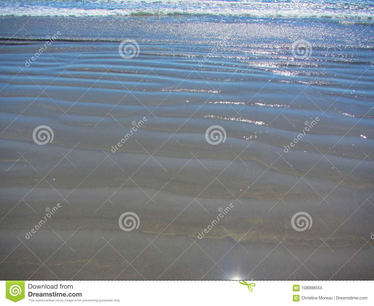 Waves And Ripples Rolling Inshore Along A Sandy Beach Stock Photo