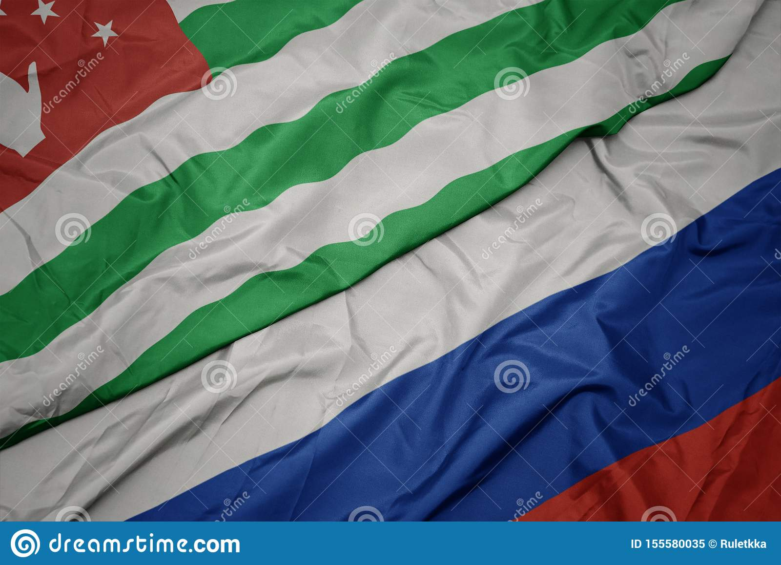 waving colorful flag of russia and national flag of abkhazia