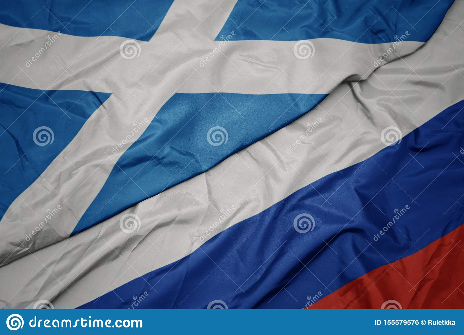 waving colorful flag of russia and national flag of scotland