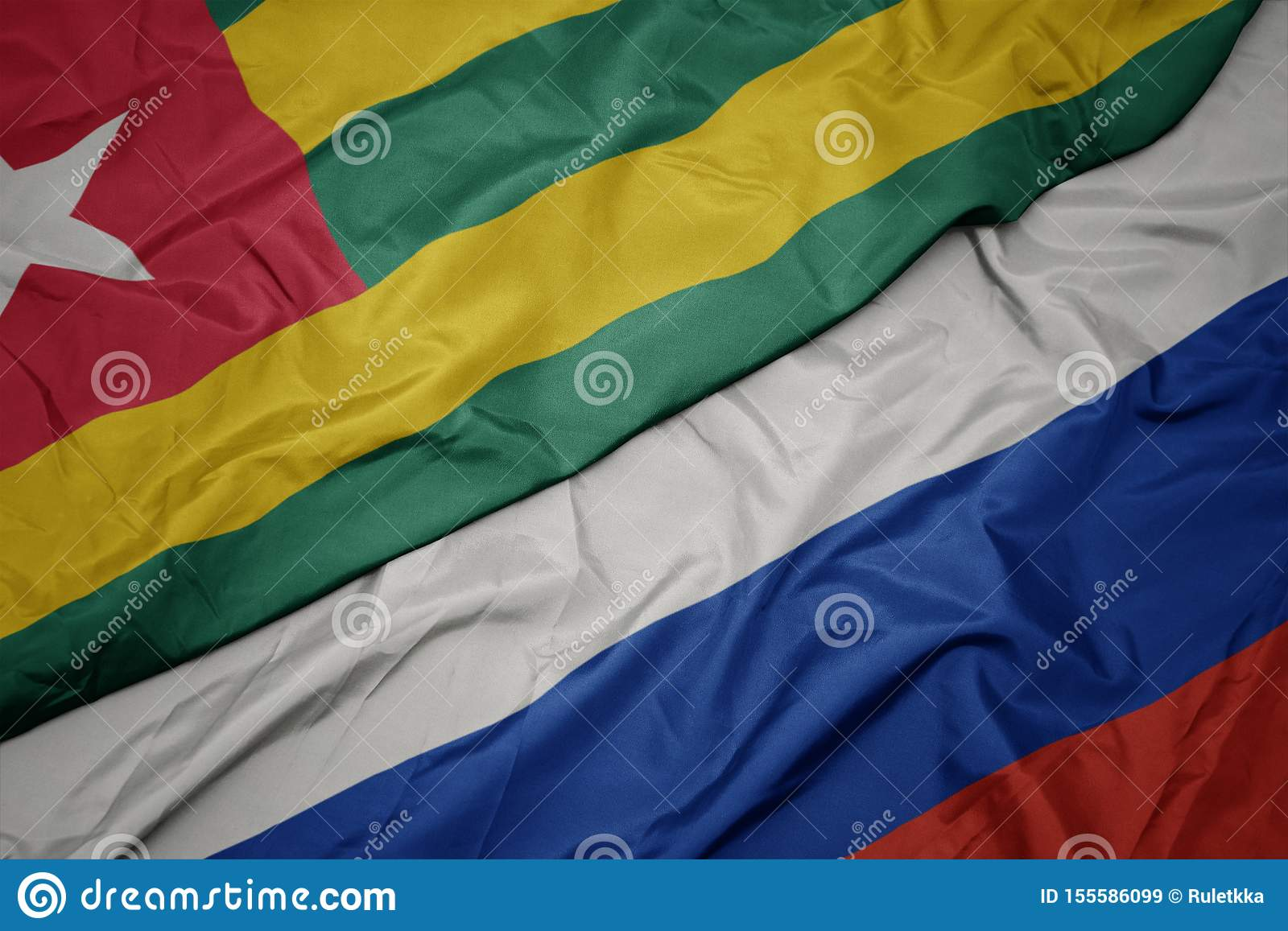 waving colorful flag of russia and national flag of togo