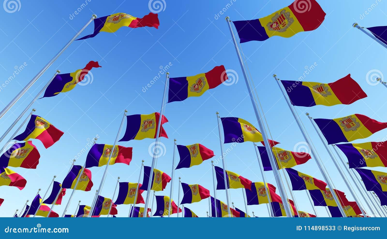 Waving Flags of Andorra against blue sky.