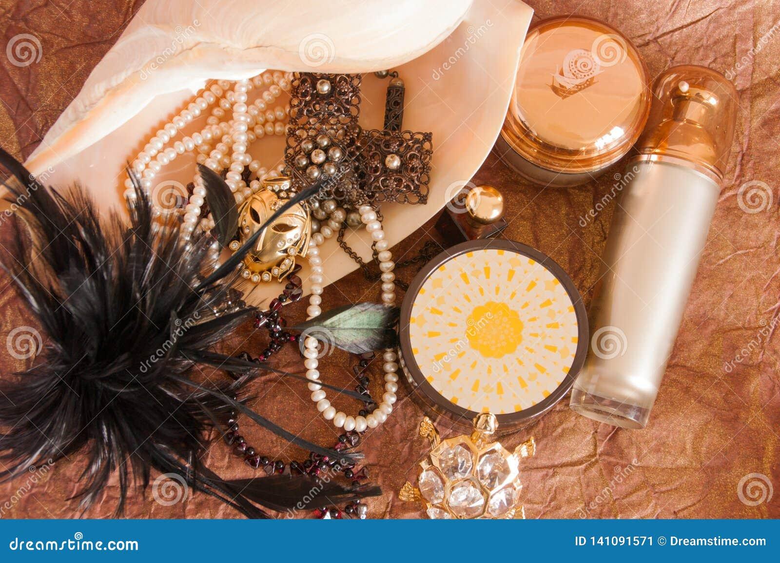 Wciąż życie piękna biżuteria w wielkiej skorupie, luksusowych skóry opieki produktach i czerni piórkach,