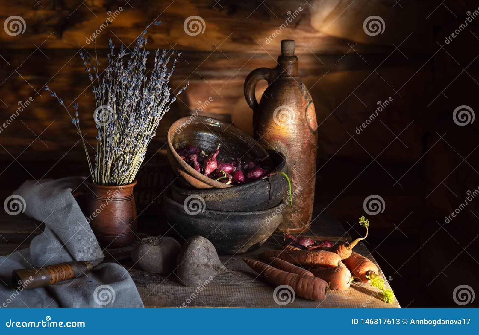 Wciąż życie w wioski budzie starzy ceramiczni naczynia i warzywa na stole w ranku słońcu