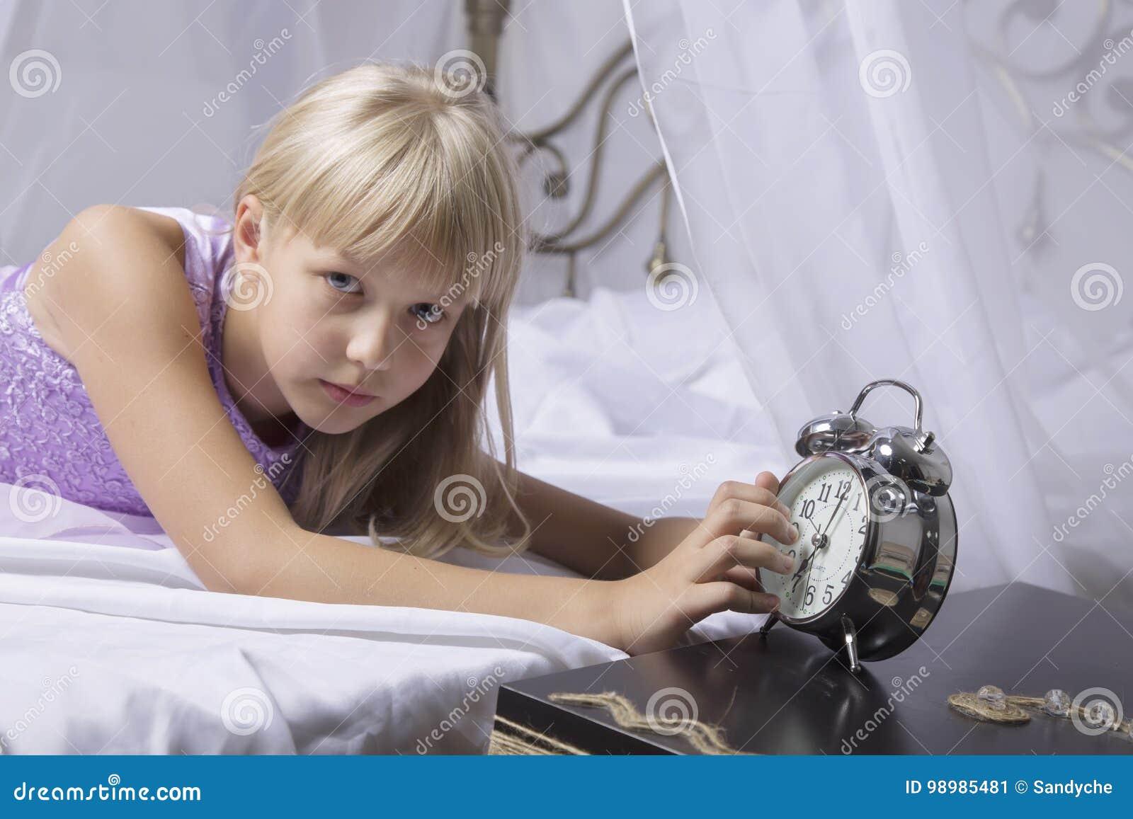 Wczesny obudzenie Budził się uśpiony młodej dziewczyny powstrzymywania budzik na łóżku w ranku