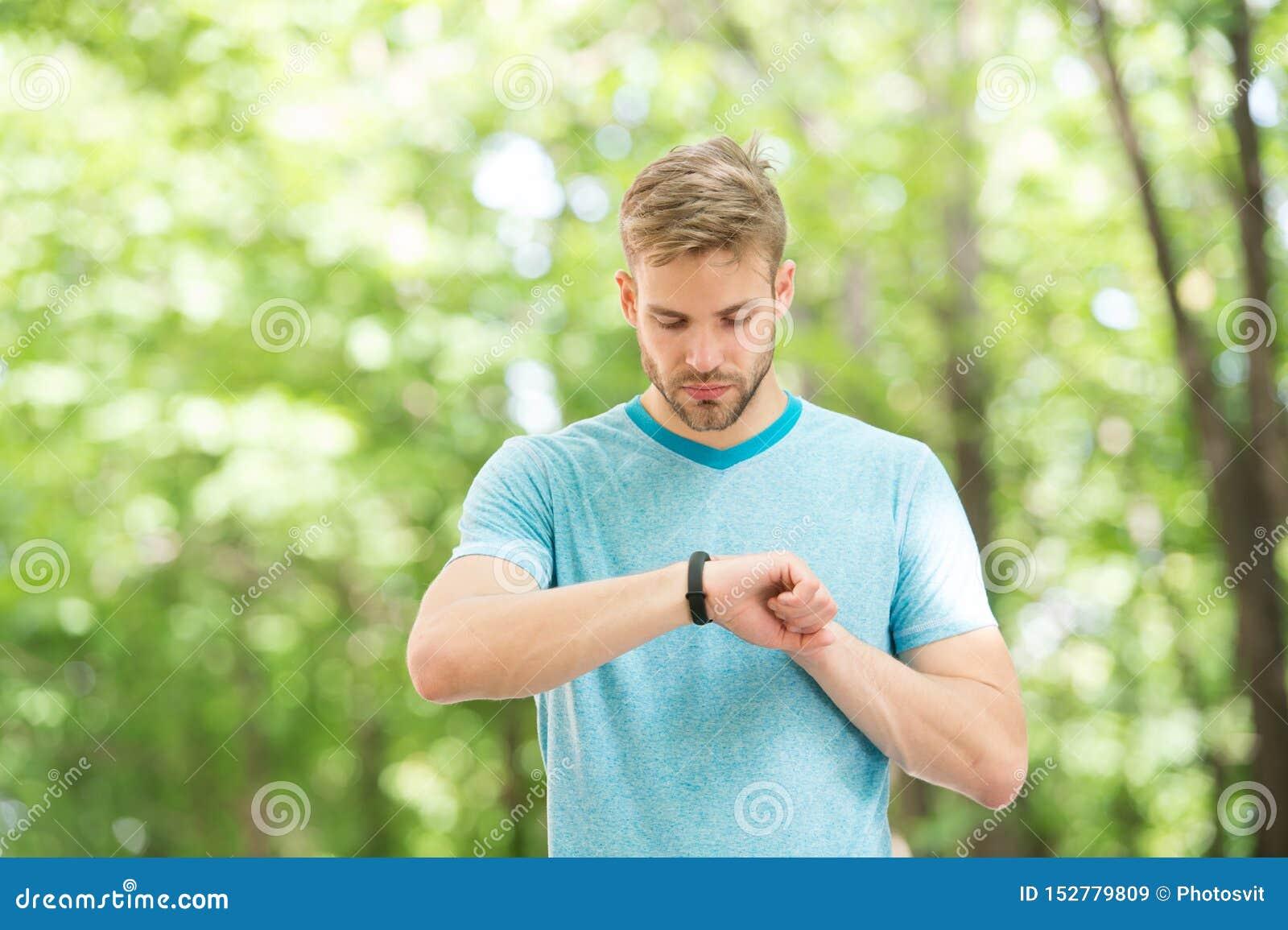 Wearable technologie Knappe atleet die smartwatch technologie gebruiken tijdens opleiding openlucht Geschikte atleet die van hem