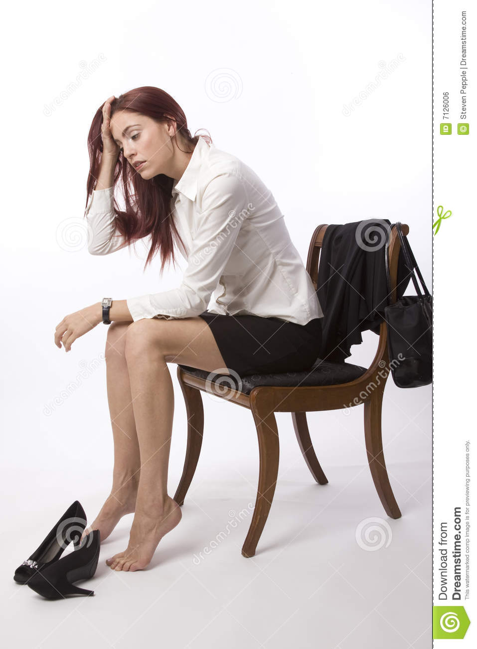 Woman in blouse and skirt sitting on chair at end of the day looking ...