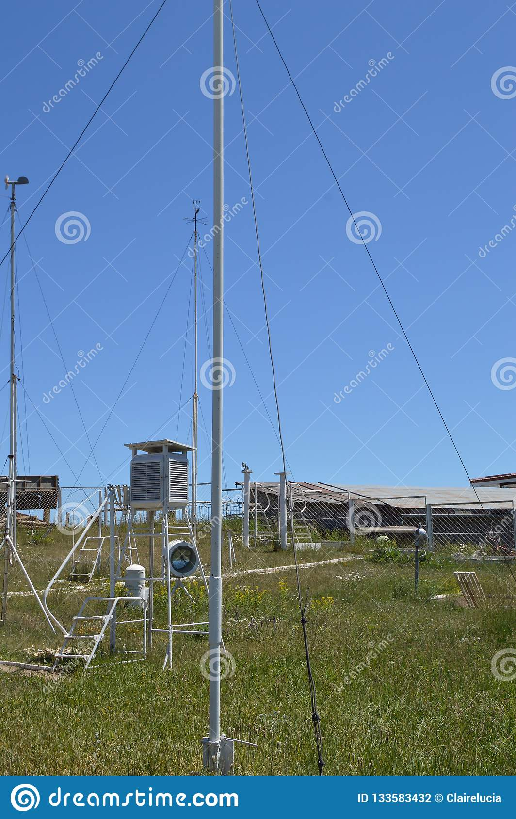 Weather station at the top of the mountain against the blue sky and grass on a Sunny summer day, vertical shot